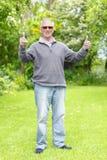 Tummar upp gamal man i trädgård Royaltyfria Bilder