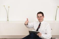 Tummar upp på kontoret på stol Royaltyfri Bild
