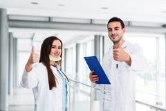 Tummar upp som motivational gest av unga medicinska kollegor arkivbild