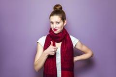Tummar upp, ung emotionell flicka med samlat hår, fräknar och röd halsduk som ser upphetsade med tummar upp på purpurfärgad bakgr fotografering för bildbyråer