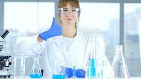 Tummar upp vid den kvinnliga forskaren i laboratorium Arkivbild