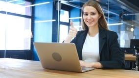 Tummar upp vid kvinnan på arbete Arkivfoton