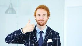 Tummar upp vid rödhårig manaffärsmannen med röda hår Arkivfoto