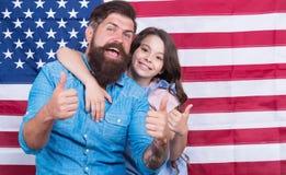 Tummar ups för självständighet Fader och litet barn som gör en gest på självständighetsdagen på amerikanska flagganbakgrund Lyckl royaltyfria bilder