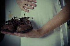 Tummy της εγκύου γυναίκας με τα αναδρομικά παπούτσια μωρών Στοκ Φωτογραφία