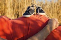 Tummy της εγκύου γυναίκας με τα παπούτσια μωρών Στοκ Φωτογραφία
