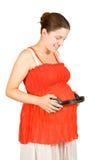 Έγκυος γυναίκα με τα ακουστικά σε tummy Στοκ Φωτογραφίες