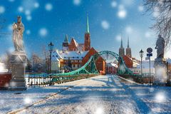 Tumski Bridge in snowy winter day, Wroclaw, Poland. Tumski Bridge and Island with Cathedral of St. John and church of the Holy Cross and St. Bartholomew in the Stock Photos