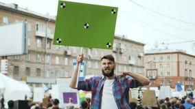Tumult i stad En pojke med en tom affisch i dina händer för din titelultrarapid stock video