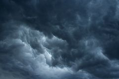 TUMULTUOUS STORM CLOUDS. Dark ominous cloud situated low in the sky with patch of light Royalty Free Stock Photo