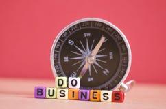 TUN Sie GESCHÄFTS-Wortwürfel und -kompaß für Geschäftsrichtungskonzept Lizenzfreie Stockbilder