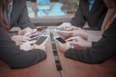 Tun Sie sich intelligentes Telefon des Gebrauches für das Treffen zusammen und besprechen Sie Abschlussbericht stockbild