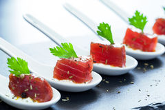 Tuna appetizers on ceramic spoons. Stock Photos
