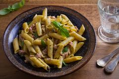 Tuna, basil and caper penne with pesto sauce in bowl on wooden background. Pasta with tuna fish. Royalty Free Stock Image