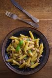 Tuna, basil and caper penne with pesto sauce in bowl on wooden background. Pasta with tuna fish. Royalty Free Stock Photo