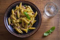 Tuna, basil and caper penne with pesto sauce in bowl on wooden background. Pasta with tuna fish. Royalty Free Stock Photos