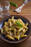 Tuna, basil and caper penne with pesto sauce in bowl on wooden background. Pasta with tuna fish. Stock Image