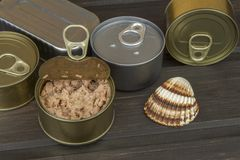 Tuna cans on a dark wooden table. Sales of canned fish. Diet food. Fishing industry Stock Images