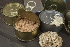 Tuna cans on a dark wooden table. Sales of canned fish. Diet food. Fishing industry Stock Photos