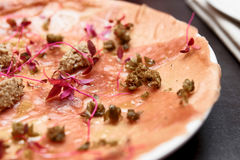 Tuna carpaccio with truffle paste and capers, toned image. Tuna carpaccio with truffle paste and capers, close-up, toned Stock Photos