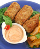 Tuna Croquettes. Crumbed tuna croquettes with sweet potatoes and a rocket salad royalty free stock images