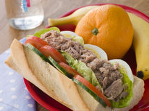 Tuna Egg and Salad Baguette with Fresh Fruit. On a table Royalty Free Stock Images