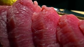 Tuna fillet pieces on wooden cutting board. 4K close-up dolly shot. Tuna fillet pieces on wooden cutting board. 4K close-up dolly video stock footage