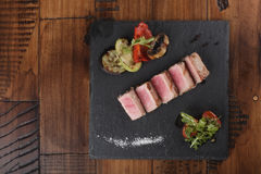 Tuna fillet slices. With salad on a slate. Wooden background Royalty Free Stock Image