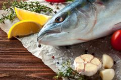 Tuna fish with herbs and vegetables. Fresh tuna head with tomatoes, lemon and spices on wooden background Stock Images