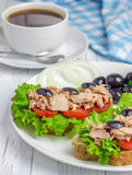 Tuna fish sandwiches on the white plate. And a cup of coffee Royalty Free Stock Photo