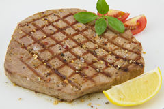 Tuna fish steak. With tomato and lemon on white background Royalty Free Stock Photography