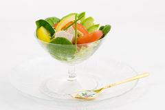 Tuna and lettuce salad. Artfully arrange lettuce,spinach, sliced avocado, red and yellow tomatoes and tuna in a champagne goblet for a special luncheon (wedding royalty free stock images