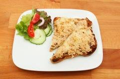 Tuna melt on table. Tuna melt on toast with salad garnish on a plate on a wooden tabletop Stock Photography