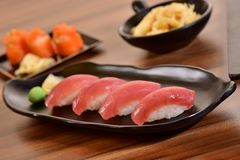 Tuna nigiri sushi plate. Tuna nigiri sushi foursome on black dishes in restaurant table Royalty Free Stock Photos