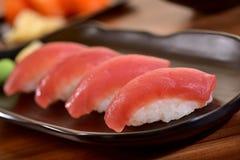 Tuna nigiri sushi plate. Tuna nigiri sushi foursome on black dishes in restaurant table Royalty Free Stock Images