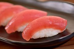 Tuna nigiri sushi plate. Tuna nigiri sushi foursome on black dishes in restaurant table Stock Photography