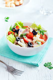 Tuna and pasta salad. With fresh tomatoes, olives, herbs in bowl over white wooden background stock photo