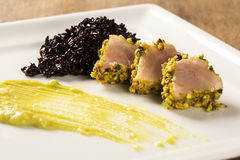 Tuna with pistachio crust, black rice and avocado puree Royalty Free Stock Photos