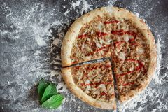 Tuna pizza and green leaves on dark background with scattered white flour. Directly above photo with copy space stock photography