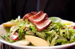 Tuna salad. Medium rare tuna fillets slice over a fresh salad made from local lettuce and heirloom tomatoes Stock Photo