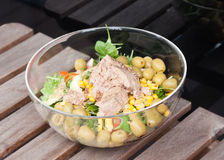 Tuna salad with corn, wild rocket, tomatoes, cucumbers, avocado. Tuna salad in a glass bowl on a wooden table Royalty Free Stock Photo