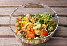 Tuna salad with corn, wild rocket, tomatoes, cucumbers, avocado. Tuna salad in a glass bowl on a wooden table Royalty Free Stock Photography