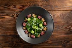 Tuna salad with matsuhisa sauce in a black plate on a wooden background stock photography