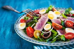 Tuna salad with tomatoes, boiled eggs, onion, anchovy and lettuc. Tuna salad  Nicoise with tomatoes, boiled eggs, onion, anchovy and lettuce Royalty Free Stock Photo