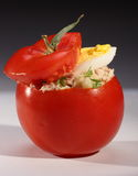 Tuna salad in tomato. Closeup of a tomato stuffed with tuna salad and a slice of hard boiled egg royalty free stock photos