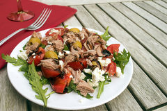 Tuna salad with tomatoes, olives and arugula, recipe in a Medite Royalty Free Stock Photo