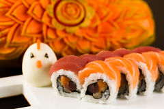 Tuna and Salmon Roll. Fancy tuna and salmon roll  on a white plate garnished with a hard boiled egg and carved papaya in the background Stock Images