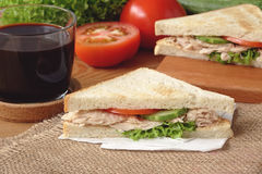 Tuna Sandwich with black coffee. Tuna sandwich, tuna, sandwich, coffee, cup, tomato, vegetable, table cloth, chopping board, cucumber, black coffee, breakfast Stock Photography
