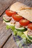 Tuna sandwich with vegetables and cheese on wooden, vertical Royalty Free Stock Photo