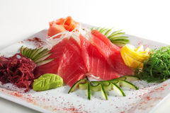 Tuna Sashimi. Sliced Raw Tuna on Daikon (White Radish) with Seaweed and Cucumber royalty free stock photography